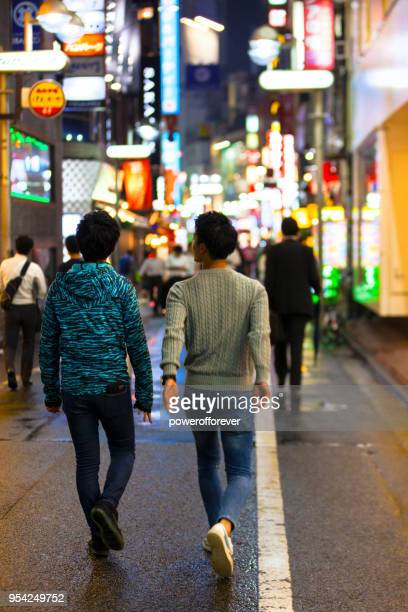 People walking through Shibuya Ward at night in downtown Tokyo, Japan