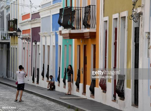 People walking through the streets of the old town are pictured on May 15 2017 in San Juan Puerto Rico as the former Spanish colony of 35 million now...