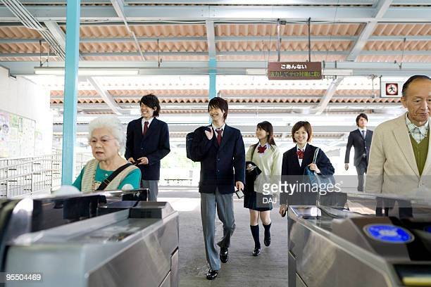 people walking through turnstiles at station - 改札 ストックフォトと画像
