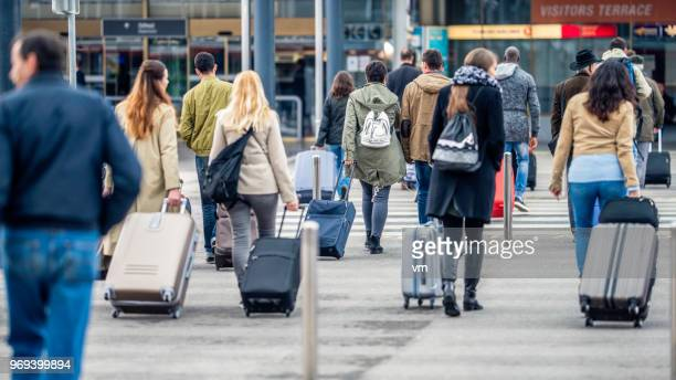 people walking towards the airport - emigration and immigration stock pictures, royalty-free photos & images