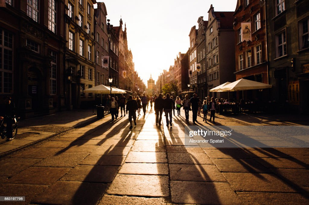 People walking towards the setting sun on an old city street : Stock Photo
