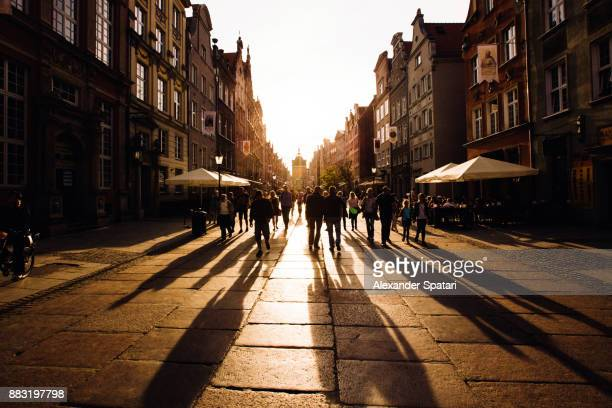 people walking towards the setting sun on an old city street - pedestrian zone stock pictures, royalty-free photos & images