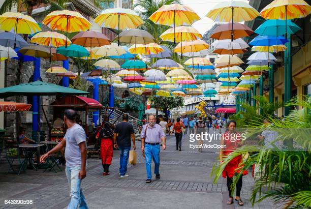 People walking under a roof of umbrellas art and design at a shopping center on December 09 2016 in Port Louis Mauritius