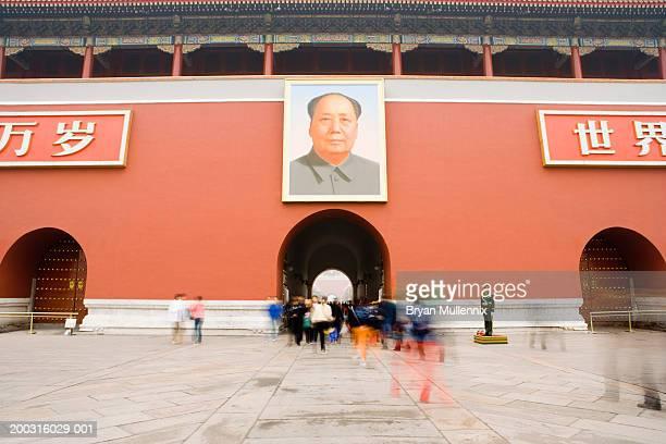 People walking under portrait of Chairman Mao at Tiananmen Gate