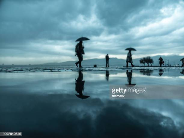 people walking under the rain in the rainy day - izmir stock pictures, royalty-free photos & images