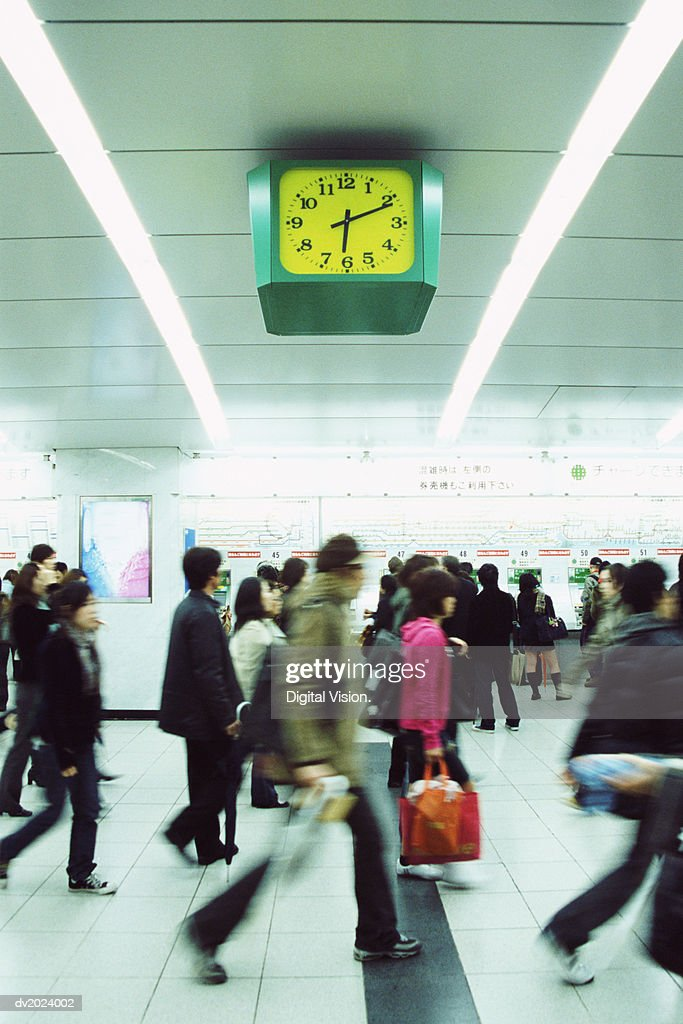 People Walking Underneath a Clock, Shinjuku, Tokyo, Japan : Stock Photo