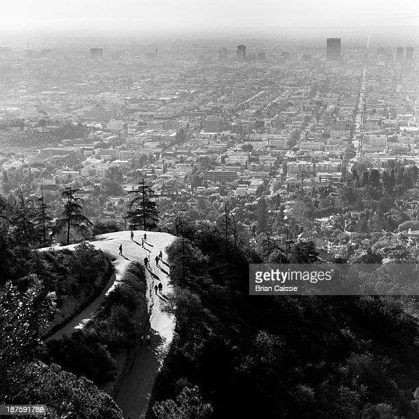 People walking up woodland hill with view of Los Angeles, California, USA
