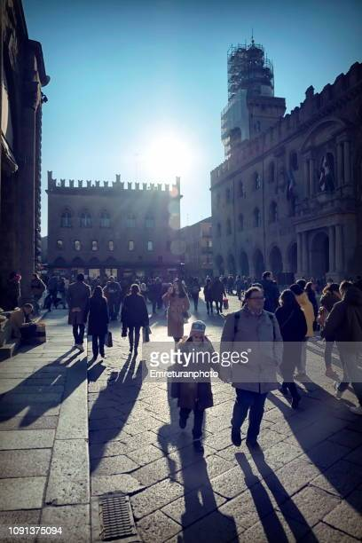 people walking with long shadows at maggiore square. - emreturanphoto stock pictures, royalty-free photos & images