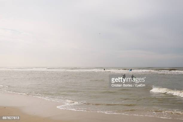 people walking with surfboards in sea - bortes stock pictures, royalty-free photos & images