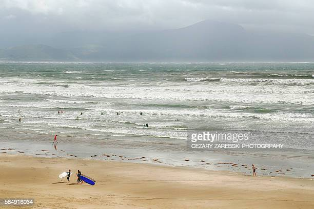 People Walking With Surfboards On The Beach In Inch On The Dingle Peninsula