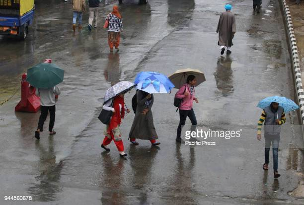 People walking with umbrellas as rain lashes Srinagar The intermittent rains continue to lash Valley since Sunday afternoon bring the mercury down...