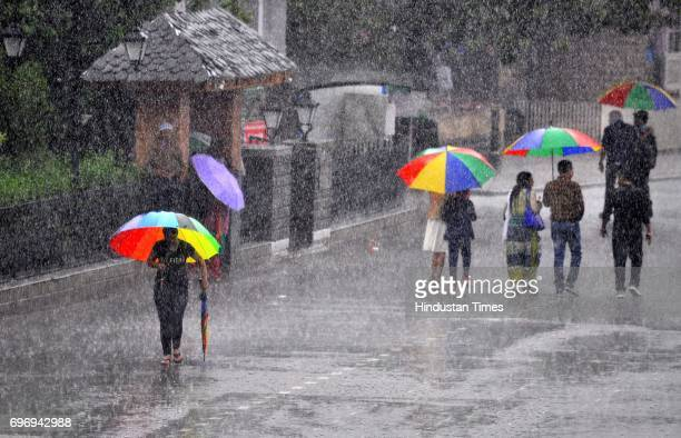 People walking with umbrellas during heavy rainfall at Ridge on June 17 2017 in Shimla India The MeT office has predicted rains or thunderstorm in...