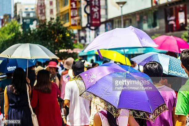 people walking with umbrellas on city street during sunny day - parham emrouz stock pictures, royalty-free photos & images