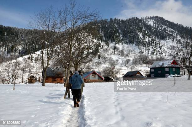 People walks over snow cover path after fresh snowfall in Daksum about 97 kilometers south of Srinagar city the summer capital of Indiancontrolled...