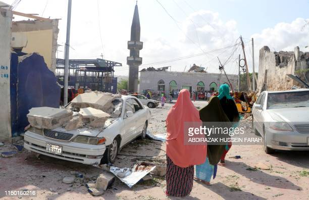 TOPSHOT People walks past a destroyed car on the site of the explosion near the Somali parliament in the capital Mogadishu on June 15 2019 A car bomb...
