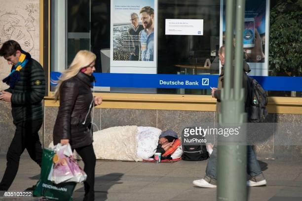 People walks past a homeless person sleeping close to an office of the Deutsche Bank close to Wittembergplatz in Berlin Germany on February 13 2017...