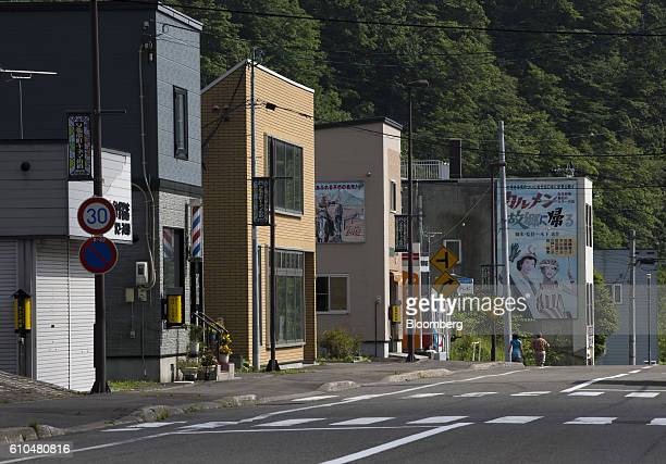 People walks past commercial buildings in Yubari Hokkaido Japan on Thursday July 21 2016 Yubari a former coalmining town in northern Japan is taking...