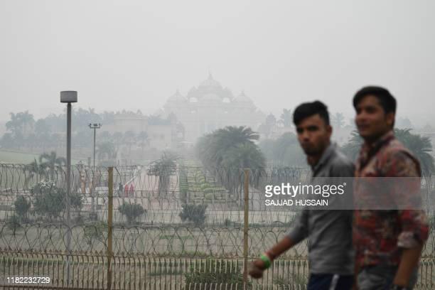 People walks past the Akshardham Hindu temple under heavy smog conditions in New Delhi on November 14 2019