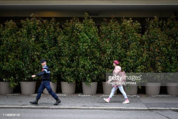 People walks past the entrance of The Fairmont Le Montreux Palace hotel hidden by plants in Montreux on May 29 which is scheduled to host the annual...