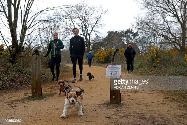 People walks their dogs as they take their daily exercise at Fleet Pond south west of London on March 29 as life in Britain continues during the...