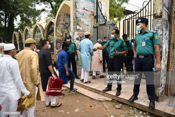 People walks through a security check post as they arrive to offer prayers to mark the start of the Muslim festival Eid al-Adha or the 'Festival of...