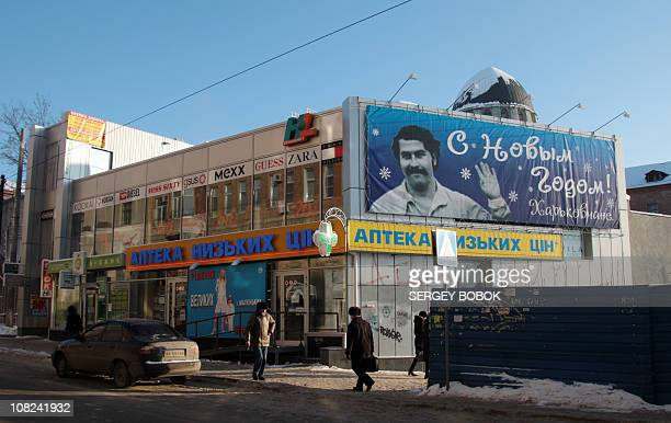 People walks under a billboard reading New Year wishes and featuring a portrait of the famous Columbian drug lord Pablo Escobar killed by the police...