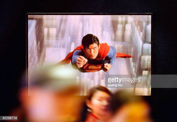 People walks under a poster of Superman during a ceremony to launch a joint venture to sell cutrate DVDs on February 24 2005 in Beijing China Warner...