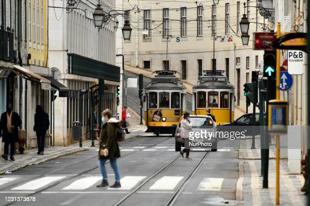 People waring protective mask walking near two trolley cars in Baixa district, Lisbon, February 25, 2021. The Portuguese government is considering a...