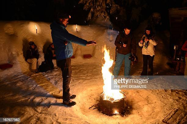 People warm around a campfire in a village of igloos at the Le Semnoz French Alps on February 23 2013 AFP PHOTO / PHILIPPE DESMAZES