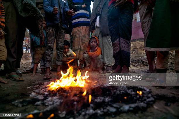 People warm themselves by a fire in a Rohingya refugee camp on January 23, 2020 in Cox's Bazar, Bangladesh. On Thursday, the International Court of...
