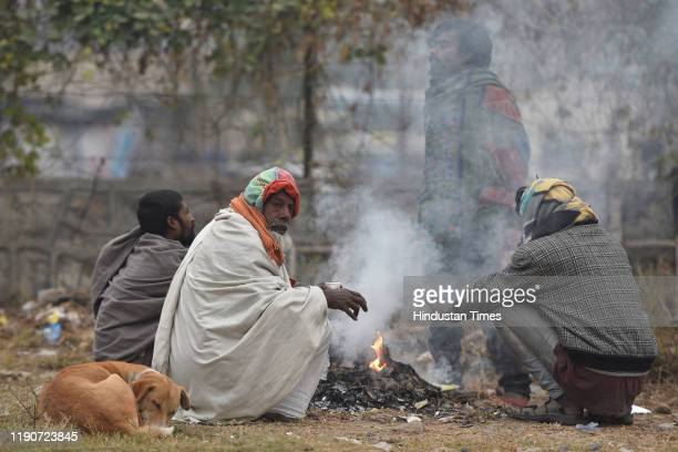 People warm themselves by a fire on a cold morning, at Sarai Kale Khan, on December 29, 2019 in New Delhi, India. Severe cold wave conditions...