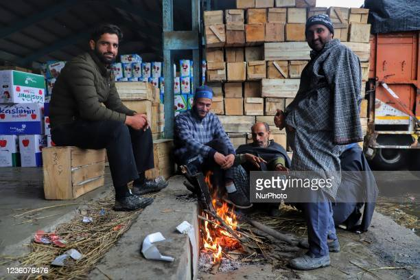 """People warm themselves during rainfall at Fruit Mandi in Sopore, District Baramulla, Jammu and Kashmir, India on 23 october 2021. """"Light to..."""