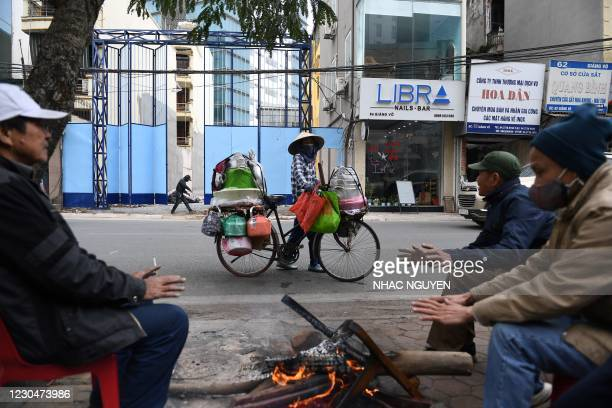 People warm themselves from a burning firewood along a street in a winter day in Hanoi on January 8, 2021.