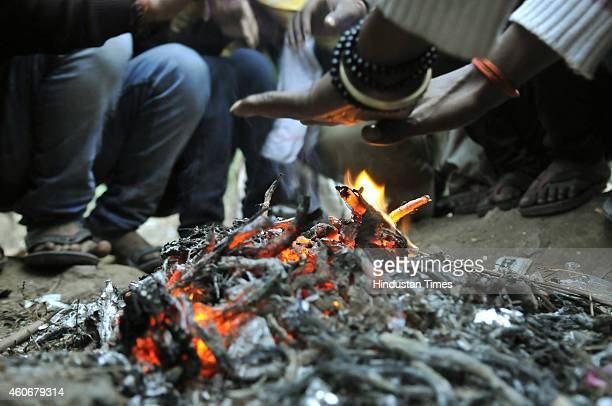 People warm themselves near a bonfire road side during a cold and foggy morning on December 18 2014 in Gurgaon India Fog and mist continued to affect...