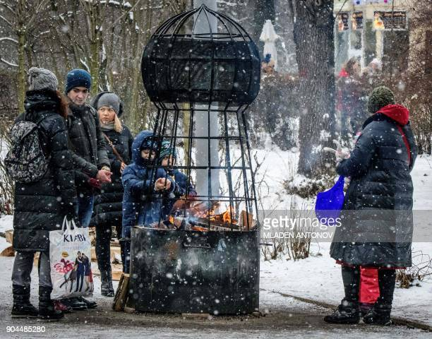 People warm up at a brazier in Sokolniki Park in Moscow on January 13 2018 / AFP PHOTO / Mladen ANTONOV