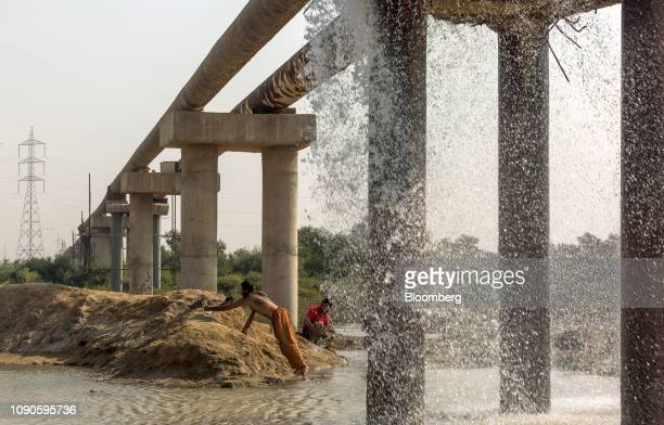 People wash clothes as water falls from a water pipe leakage in Karachi Pakistan on Monday Dec 24 2018 Women and children walk miles each day in...
