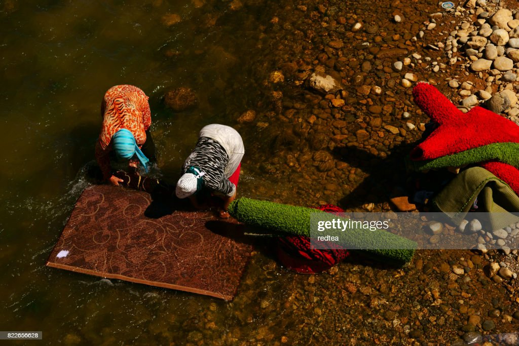 People wash the carpets alongside the river in rural area : Stock Photo