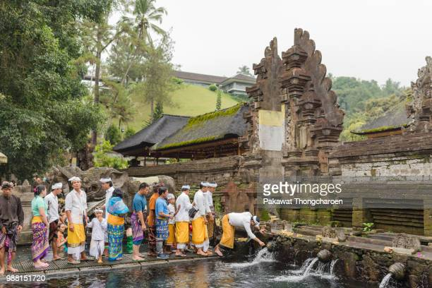bali, indonesia - june 19, 2018: people washing holy water at pura tirta empul temple - pura tirta empul temple stock pictures, royalty-free photos & images