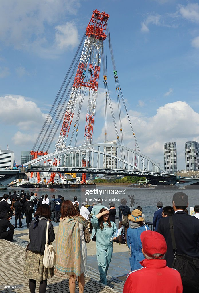 People watch a 2,600-ton new bridge built across Sumida River on May 8, 2014 in Tokyo, Japan. The 120-meter bridge, assembled at Yokohama Port not to disturb the traffic of the Sumida River, will be part of Loop Line 2 which is an expected major traffic artery linking major venues at the 2020 Tokyo Summer Olympics.