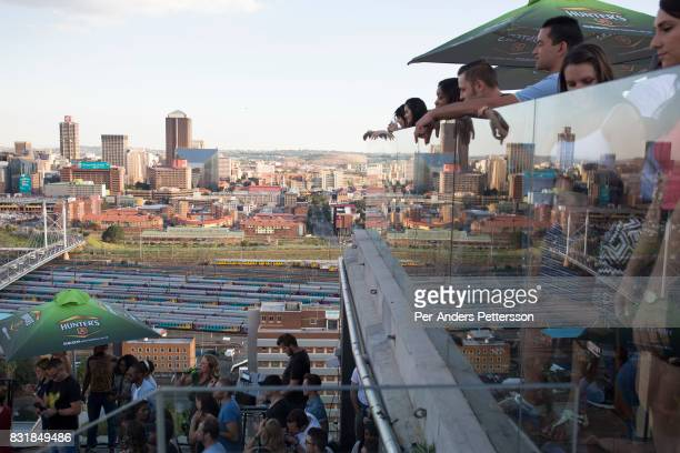 People watch a band perform on a rooftop bar on March 19 2016 in downtown Johannesburg South Africa The area is a culture hub with many students...