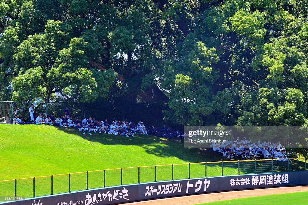 People watch a baseball game under the shade of trees to avoid a strong sunshine at Fujisakidai Stadium on July 9, 2013 in Kumamoto, Japan. Koshu City of Yamanashi reached 39.1 degrees Celsius and two-third of the 927 Japan Meteorological Agency's observation points recorded more than 35 degrees, killing three people by heat disorder.