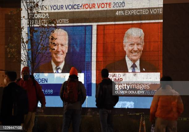 People watch a big screen displaying the live election results in Florida at Black Lives Matter plaza across from the White House on election day in...