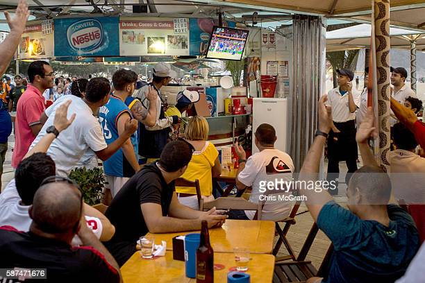 People watch a Brazilian athlete win gold on the tv in a beachside cafe at Copacabana Beach on August 8 2016 in Rio de Janeiro Brazil Olympic team...