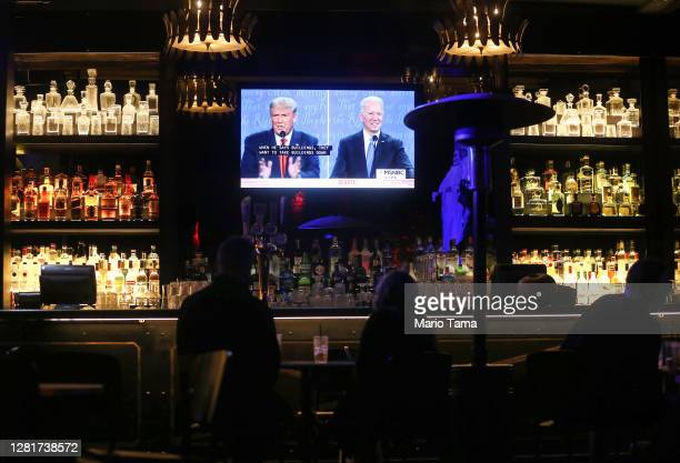 People watch a broadcast of the final debate between President Donald Trump and Democratic presidential nominee Joe Biden at The Abbey, with socially...