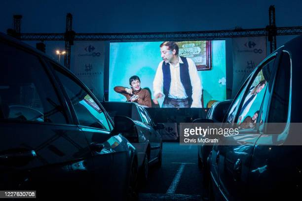 People watch a classic Turkish movie from their cars at a temporary drive-in theatre held in a shopping mall car park amid the ongoing Covid-19...