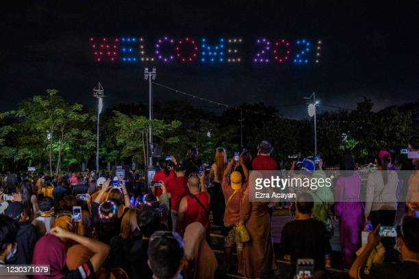 People watch a drone show during New Year's Eve celebrations at a park on January 1, 2021 in Manila, Philippines. Philippine authorities have urged...