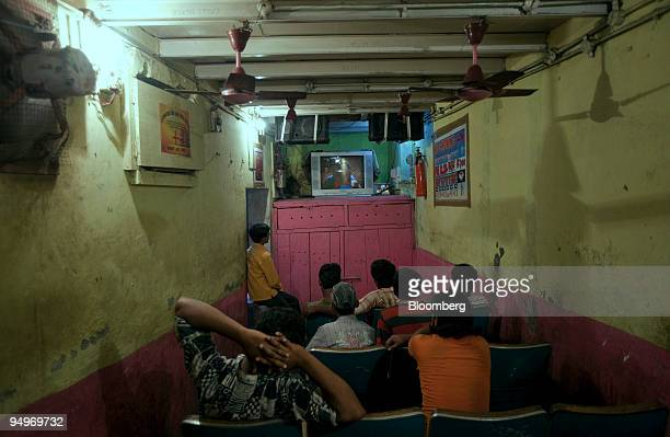People watch a film in a room converted into a movie theatre in the Dharavi slum area of Mumbai India on Saturday July 2009 Of the 19 million people...