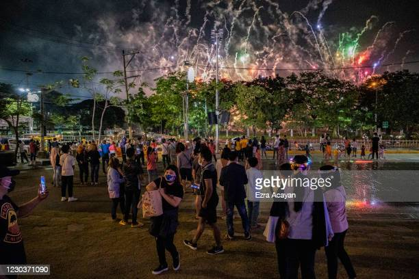 People watch a fireworks display during New Year's Eve celebrations at a park on January 1, 2021 in Manila, Philippines. Philippine authorities have...