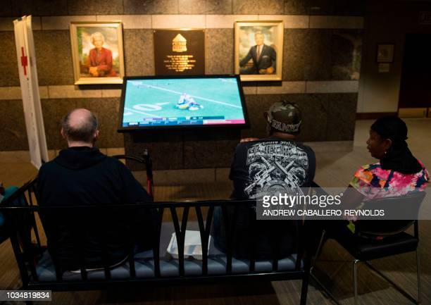People watch a football match inside an American Red Cross evacuation shelter in Chapel Hill North Carolina on September 17 2018 Catastrophic floods...