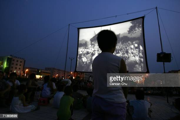 People watch a free movie at an openair cinema at a square after an earthquake July 4 2006 in Wen'an County Hebei Province of China An earthquake...